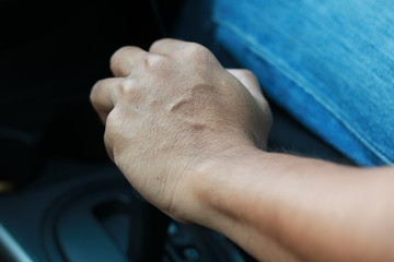 Hand hold gearshift in car.