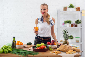 Woman preparing dinner in a kitchen, drinking juice concept cooking, culinary, healthy lifestyle.