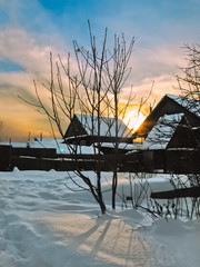 Picturesque sunset in the village in the winter evening