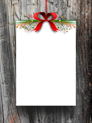 Blank frame hanged by red Christmas ribbon against dark wooden background