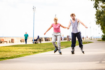Young couple rollerblading in park holding hands.