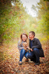 Young happy attractive couple posing with their dog yorkshire terrier