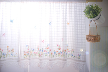 A kitchen windows dressed with lace curtain and flower pot, with sun flare effect