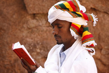 Faithful reading outside a church in Lalibela, Ethiopia, Africa