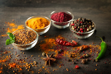 Aromatic spices in glass bowls on grey background