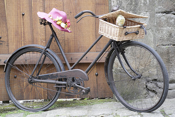 Old bicycle with a basket and a pink straw hat