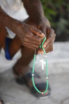Haitian woman praying with prayer beads, Port au Prince, Haiti