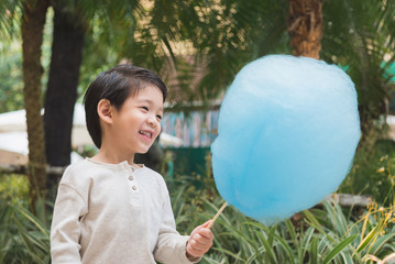 Cute Asian child eating cotton candy