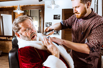 Santa claus shaving his personal barber