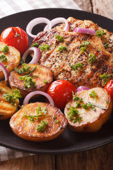 Chicken steak with grilled new potatoes and tomatoes close-up. vertical