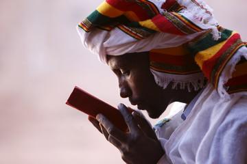 Faithful kissing a Bible outside a church in Lalibela, Ethiopia, Africa