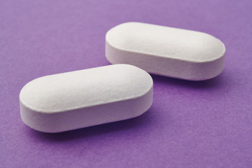 Pills over a purple background. Medicament treatment. Health car