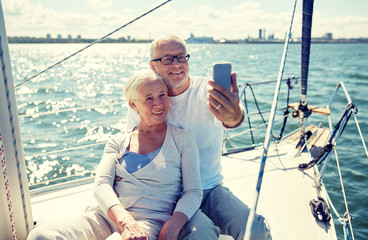 seniors with smartphone taking selfie on yacht