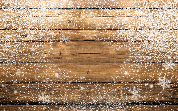 wooden background with snowflakes and snow