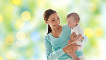 happy mother with little baby over green lights