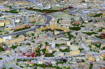City scale model, dron view of town miniature, layout of urban space with houses and buildings with lights, highways, roads, river, bridges, streets, trees, transport traffic, architectural background