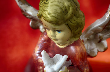 Angel with dove. Ceramic figurine of an Angel with a pigeon in his hands. Close-up image for Christmas decoration.