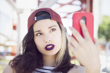 Beautiful young woman taking a self portrait with mobile phone outdoors