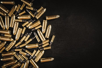 bullets from the gun placed on a black wooden table