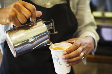 Close up of hot milk being poured from a jug into a paper cup.
