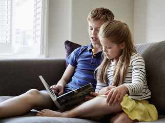 Two children sitting side by side reading  book
