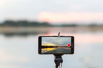 using smart phone take a photo of sunset landscape on lake