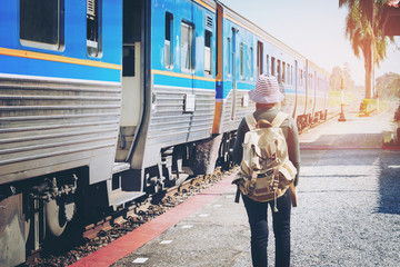 Traveler woman walking and waits train on railway platform