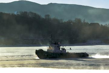 marine tug floats on the sea freezes along the ice floe with the fishermen