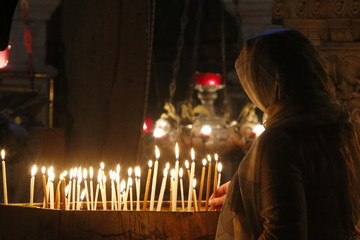 Pilgrim lighting candles in the Holy Sepulchre Church, Jerusalem, Israel, Middle East