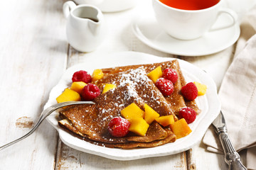 Crepes with fresh mango and raspberries