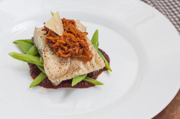 Cooked fish with steamed asparagus, vegetable ragout, tomato sauce and potato chips. Wooden background. Top view. Close-up