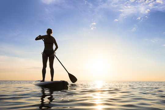 Girl stand up paddle boarding (sup) on quiet sea, sunset