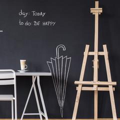 Desk and easel against blackboard wall