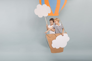 Creative siblings in paper balloon