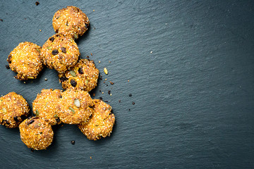 Cereal Cookies with Seeds, Raisins, Nuts and Sezam on Dark Stone Background, Top View, Free Space for Your Text