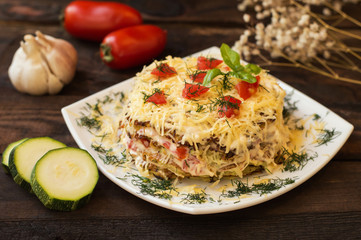 The cake of zucchini with cheese, tomato and basil. Wooden background. Close-up