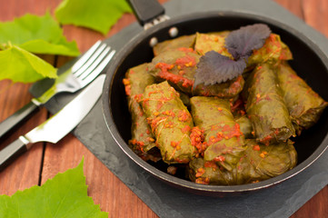 Dolma in the pan - this grape leaves stuffed with rice-based, as well  boiled minced meat. It is common in kitchens Caucasus, the Balkans, Asia and North Africa.Wooden background. Close-up