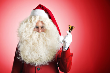 Santa Claus with huge pretty beard in red hat and coat ringing a golden bell in left hand with white glove, isolated on red background