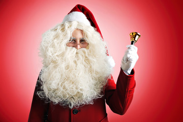 Santa Claus with huge pretty beard in red hat and coat ringing a golden bell on red background