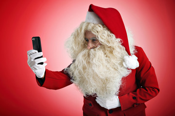 Santa is trying to see something on small screen of his new smartphone while taking photo or video, isolated on red
