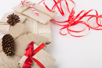 Christmas boxes with gifts tied with ribbon and pine cones isolated on white background