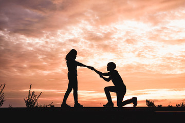 Silhouette of man propose to his girlfriend in the sunset backgr