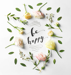 "Quote ""Be happy"" written on paper with leaves and flowers on white background. Top view"