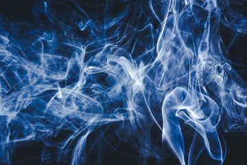 Artistic blue smoke on black background texture.