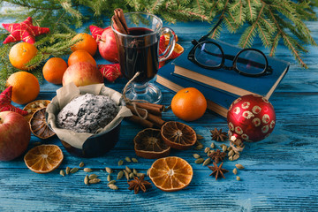 Mulled wine, spices and nuts on blue background