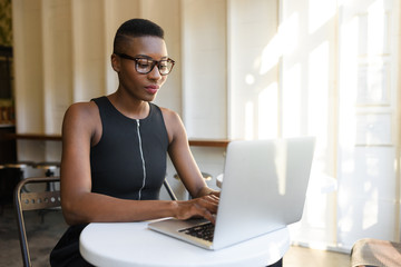 Young fashionable african business woman working hard at the cafe on the laptop