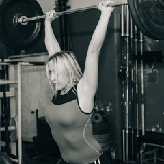 Female on weightlifting training. Female lifting weights