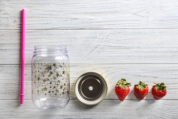 Empty mason jar with strawberries on wooden background