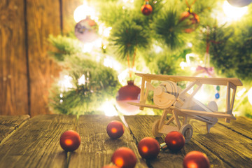 Christmas holiday background with wooden airplane and christmas red balls on wooden table top over festive bokeh light decorate on Christmas tree.