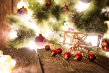 Christmas tree and christmas lights with presents and handmade wooden airplane toys on wooden table